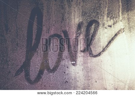 Texture water drops are on a gleam and light through the misted over window. The word