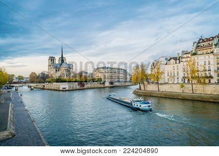 Notre-dame-de-paris, The Seine River And A Boat In Paris In Autumn