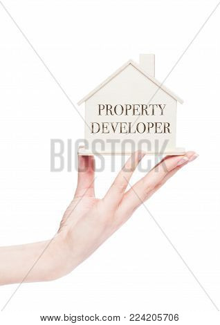 Female hand holding wooden house model with conceptual text.  Real Estate Agency