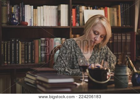 Mature blonde lady writing down notes, studying or writing a book and holding a glass of wine in an intimate private library surrounding