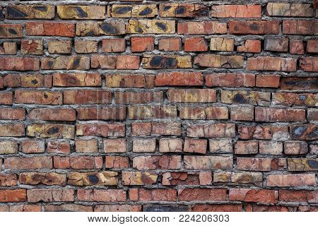 Old ragged and dilapidated brick wall with dirty black spots and cracks.  Brickwork as a background and texture.