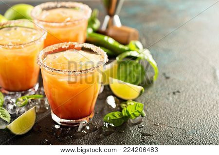 Spicy tequila sunrise margarita cocktail with lime and hotpepper