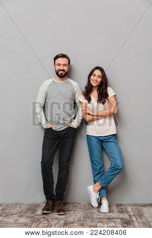 Full length portrait of a smiling young couple standing together and looking at camera over gray background