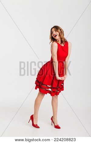 Full length portrait of a joyful petty girl dressed in red dress posing while standing and looking away at copy space isolated over white background