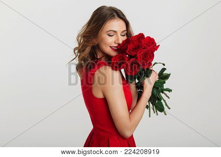 Portrait of an attractive young woman dressed in red dress holding bouquet of roses isolated over white background