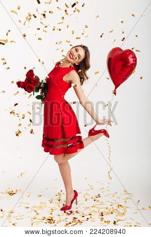 Full length portrait of a satisfied young woman dressed in red dress holding bouquet of roses and air balloons while standing under falling confetti and celebrating isolated over white background