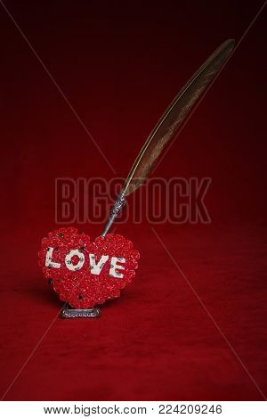 Heart writings, golden quill for the most beautiful poems and words, envelope, quill on a dark red background