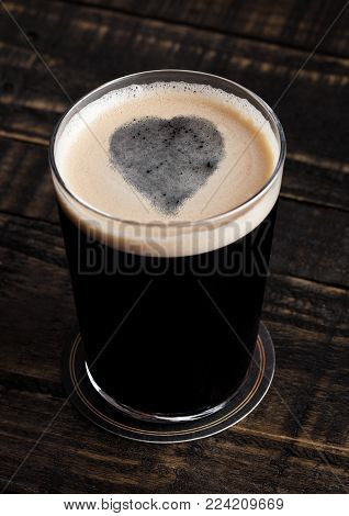 Glass of stout beer top with heart shape on wooden background