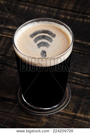 Glass of stout beer top with wi-fi symbol shape on wooden background