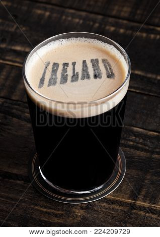 Glass of stout beer top with ireland letters shape on wooden background