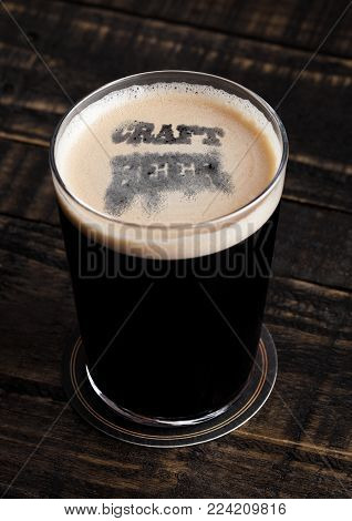 Glass of stout beer top with craft beer letters shape on wooden background