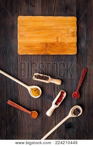 Make menu or write recipe. Mock up for menu or recipe. Wooden cutting board near spices and ingredients on dark wooden background top view.