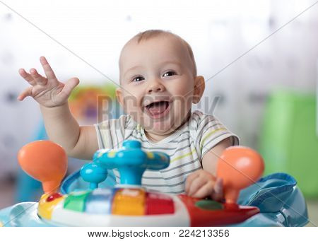 funny baby boy playing in baby walker at home