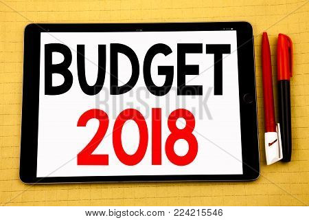 Conceptual handwriting text caption inspiration showing Budget 2018. Business concept for Household budgeting accounting planning Written on tablet, wooden background with sticky note and pen