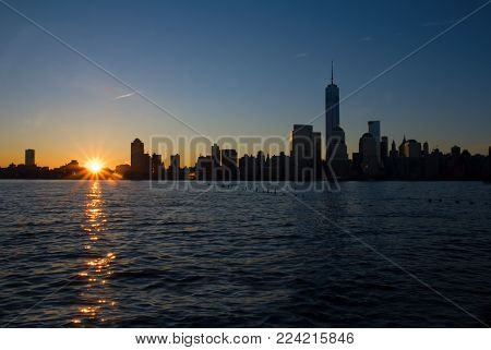 The skyline of lower Manhatten with the sun rising over buildings and the Hudson River.