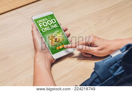 People order food online with mobile apps on wood table at home,online food delivery technology in daily lifestyle,Digital age concept