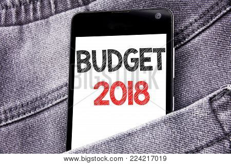 Hand writing text caption inspiration showing Budget 2018. Business concept for Household budgeting accounting planning written mobile cell phone with space in the back pants trousers pocket