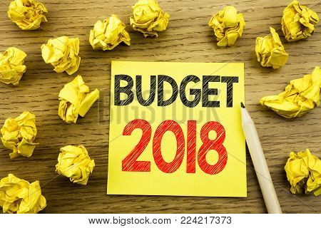 Word, writing Budget 2018. Business concept for Household budgeting accounting planning written on sticky note paper on wooden background. Folded yellow papers on the background
