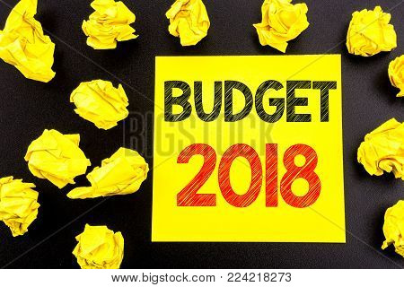 Conceptual hand writing text showing Budget 2018. Business concept for Household budgeting accounting planning written on sticky note paper on black background. Folded yellow papers on the background