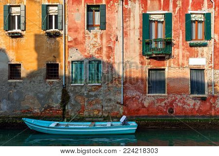 Boat on small canal moored against old colorful brick house in Venice, Italy.