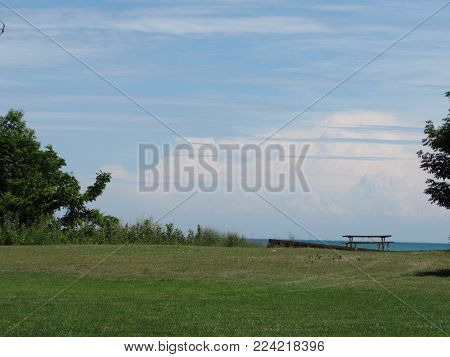 A green field and clouds over Lake Erie.