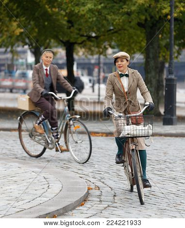 STOCKHOLM - SEPT 23, 2017: Elegant bicycling women dressed in traditional tweed jacket on a cobblestone street in the Bike in Tweed event September 23, 2017 in Stockholm, Sweden