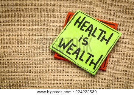 health is wealth reminder - handwriting on a sticky note against burlap canvas