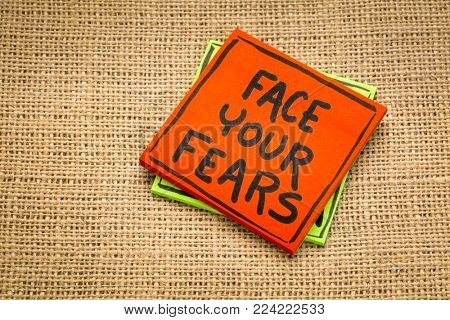 face your fears reminde - handwriting on a sticky note against burlap canvas