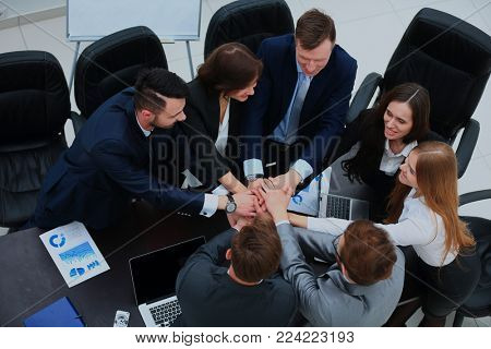 Business team showing unity with their hands together.