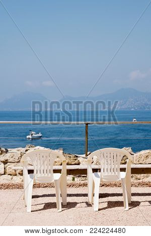 some plastic chairs in the Ile Saint-Honorat facing the Mediterranean sea, with Cannes in the background, in the famous French Riviera