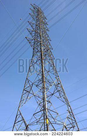 steel frame of high voltage tower pole and transmission electrical power lines with red and white ball for aircraft warning and blue sky background