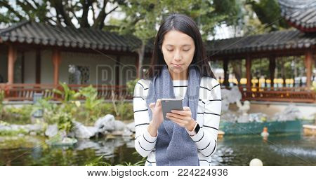 Woman using smart phone in Chinese garden , sending sms on cellphone