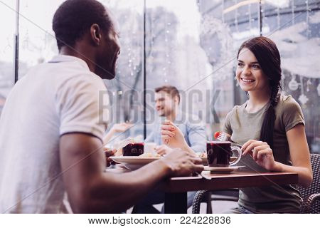 Pleasant lunch. Pleased satisfied irresistible woman holding fork while smiling and staring at man