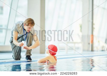 Young trainer explaining little swimmer what to do in extreme situation in water