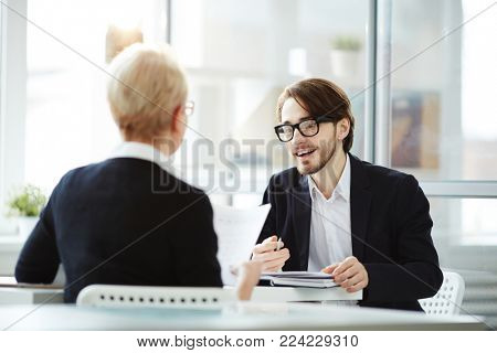 Young elegant applicant talking to employer and explaining some details of his previous job