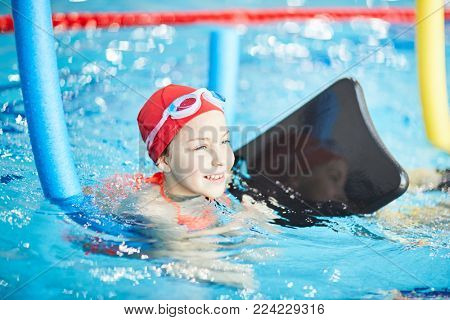Adorable girl in swimwear practicing swimming with special resistance equipment