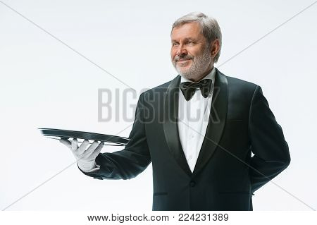 Senior waiter holding tray and standing isolated on white studio background. concept of good service