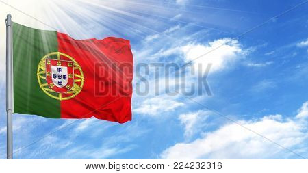 Flag of Portugal on flagpole against the blue sky.