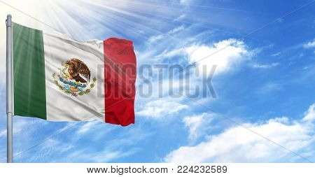 Flag of Mexico on flagpole against the blue sky.