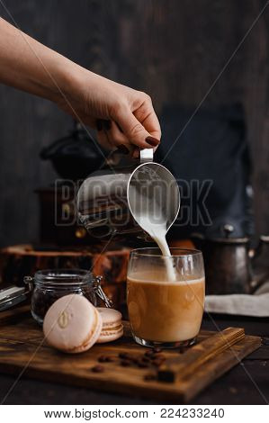 Coffee. Breakfast. Hand of girl pours milk into coffee, next to macaroni, in background coffee grinder, coffee beans, gray background, loft style. vertical frame. Instagram
