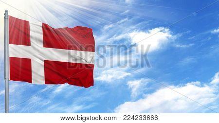 Flag of Denmark on flagpole against the blue sky.
