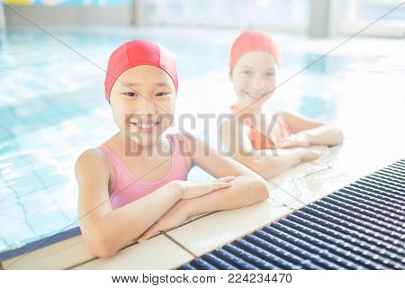 Little girls in swim-caps and swimwear enjoying training in swimming-pool after classes