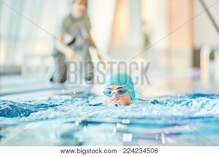 Young boy in goggles and swim-cap practicing swimming on instructions of his trainer