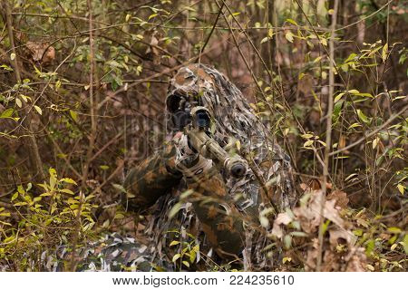 Hunter or soldier hiding in bushes, autumn forest background. Sniper with rifle.