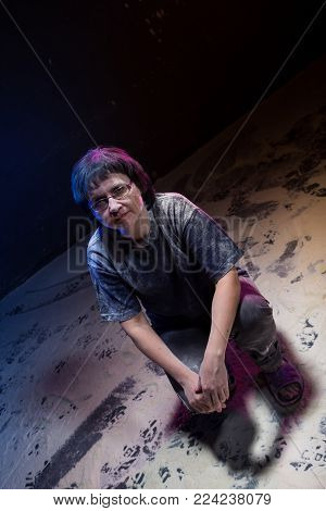 Girl in chalk-stained clothes in a dark room and chalk on the floor