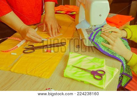 Sewing machine. sewing process in the phase of overstitching. Dressmaker work on the sewing machine. Tailor making a garment in workplace. Hobby sewing fabric as a small business concept