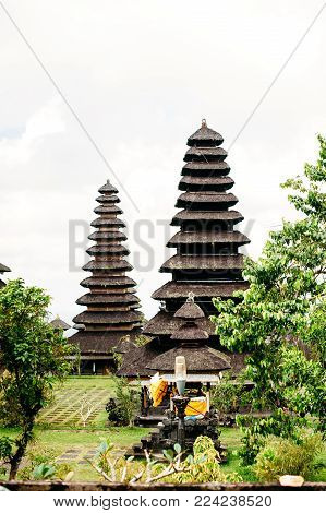Temples in Pura Penataran Agung Besakih complex, the mother temple of Bali Island, Indonesia. Green lawn with several balinese temples with multistage roofs. Travel and architecture background. Vertical photo