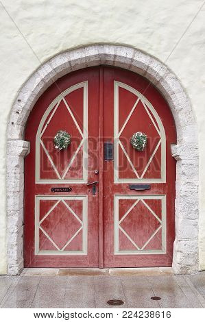 Red old fashioned wooden door on white facade. Tallinn. Estonia