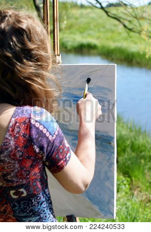 Close Up Of Woman Artist Painting River Landscape On Canvas On Summer.