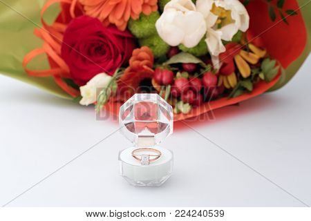 Engagement ring in a gift box with bright bouquet of flowers. The offer to get married. Gift for St. Valentine's Day. Marriage proposal for beloved woman. Symbol of love and marriage
